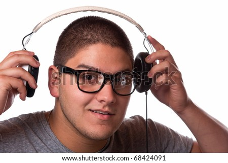 A young man listens to music with a set of head phones. - stock photo