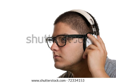 A young man listens to music with a set of head phones while examining the album cd case. - stock photo