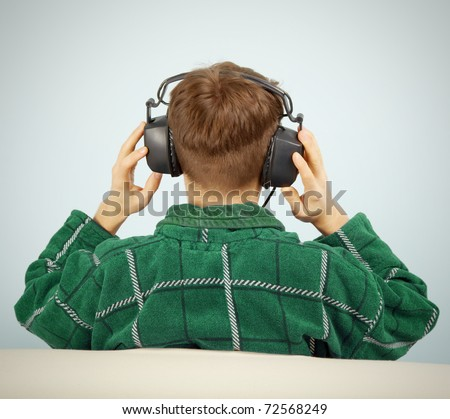 A young man listens to symphonic music at home on the couch - stock photo