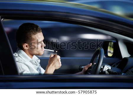 A young man lit a cigarette in a car at speed - stock photo