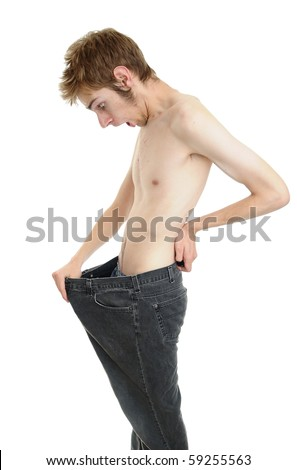 A young man looking down at his old pants when he was fat. Looks like he lost some weight and is now thin! Isolated on white.