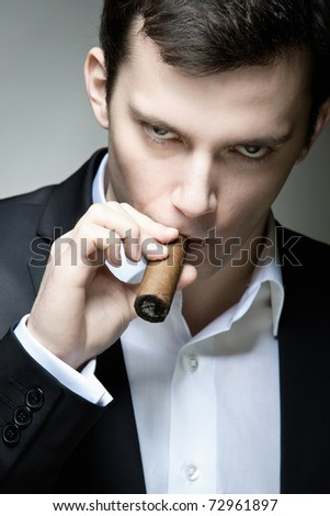 A young man looking suspicious with a cigar - stock photo