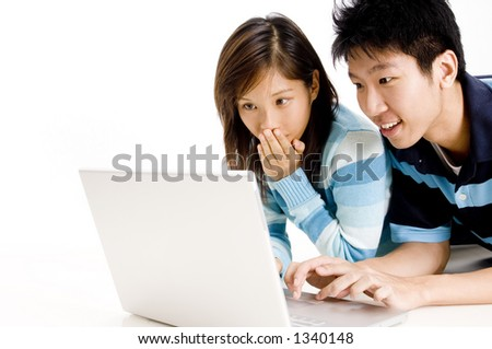A young man looks at something shocking on his laptop computer