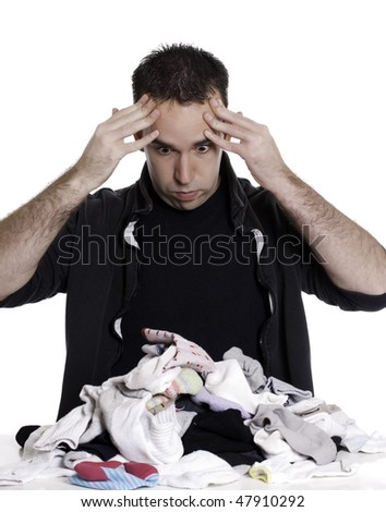 A young man looks frustrated at having to sort laundry or socks, isolated against a white background.