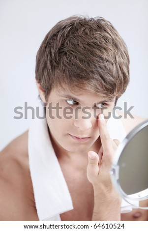 A young man looks in the mirror in the bathroom - stock photo