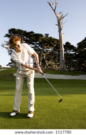 A young man looks on after the putt he has just made - stock photo