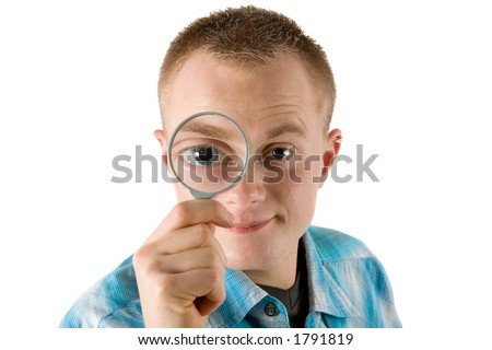 a young man looks through a magnifying glass - stock photo