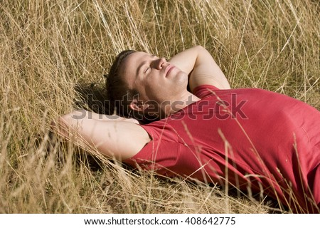 A young man lying in the sun - stock photo