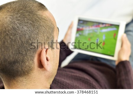 a young man lying on the couch watches a soccer match in streaming in his tablet computer - stock photo