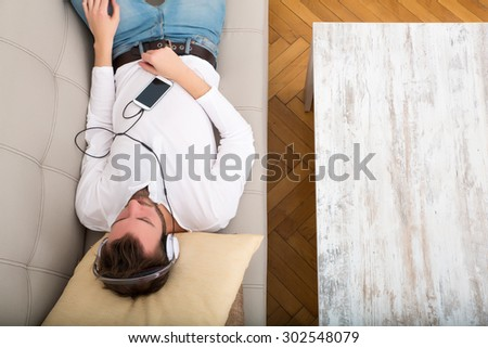 A young man lying on the sofa listening to music with some headphones and a smartphone.