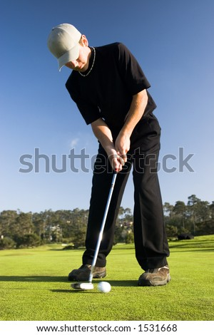 A young man makes a putt - stock photo