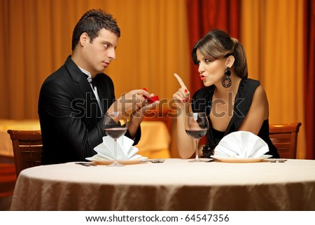 A young man making a proposal to his girlfriend in a restaurant - stock photo