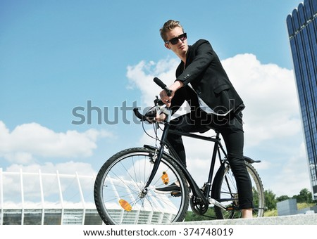 A young man on a bicycle in the street - stock photo
