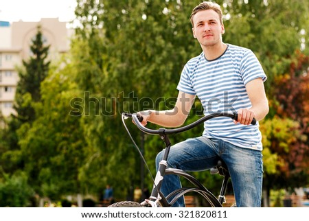A young man on a bicycle looks into the distance in city park