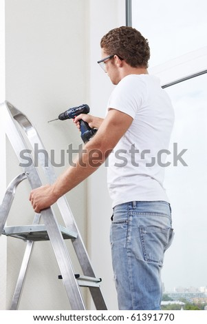 A young man on a ladder working with a drill