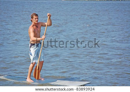 A young man on his paddle-board in the intracoastal river in Florida. - stock photo