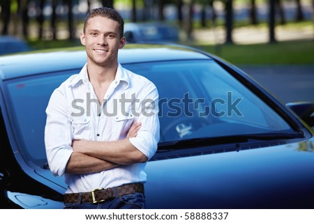 A young man on the background of cars