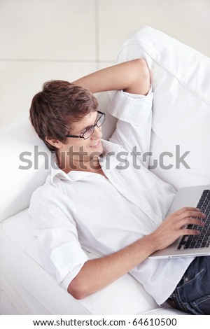 A young man on the couch with a laptop works - stock photo