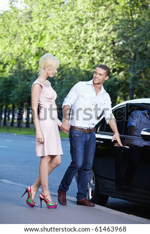A young man opens the car door in front of a girl - stock photo