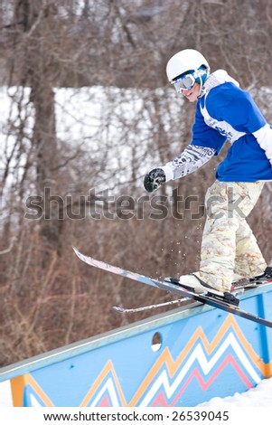 A young man performs a rail slide on skis. - stock photo