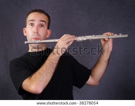 A young man playing a metal flute which is a wind instrument - stock photo