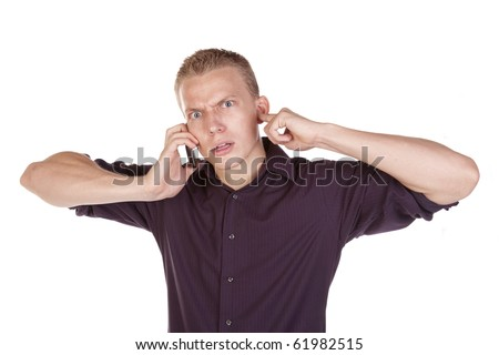 A young man plugging his ears trying to  listen to the person on his phone. - stock photo