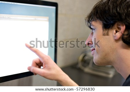 A young man pointing at a modern computer monitor lcd with copy-space.  Shallow depth of field with strongest focus on the face. - stock photo
