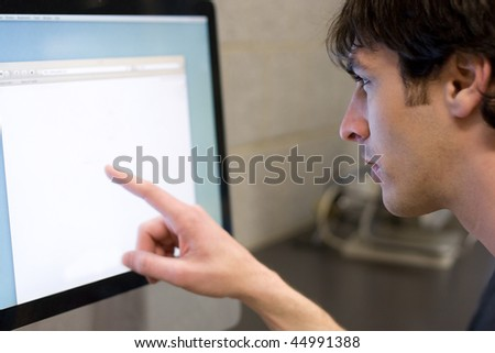 A young man pointing at a modern computer monitor lcd with copyspace.  Shallow depth of field with strongest focus on the face.