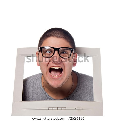 A young man popping his head out of a computer monitor with nerd glasses. - stock photo