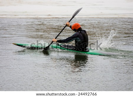 A young man power strokes his way down a still half frozen river, as he practices for his next competition.