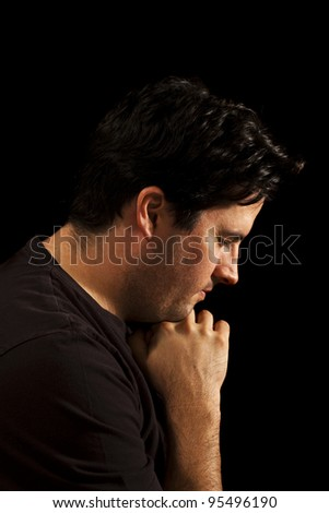 A young man prays - stock photo