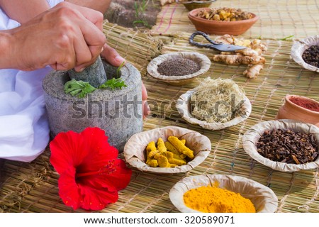 A young man preparing ayurvedic medicine in the traditional manner in India  - stock photo