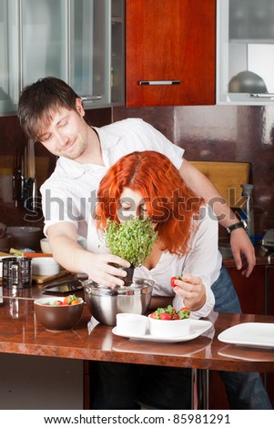A young man presents potted thyme to his girlfriend while she eats strawberry and ready to cook - stock photo