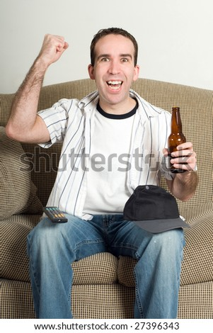 A young man pumping his fist with excitement as he watches tv and enjoys his beer
