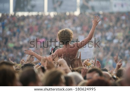 A young man raised by the crowd during a concert - stock photo