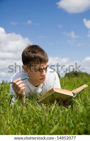 A young man reads a book, lying on a grass.