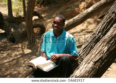 a young man reads a book outside - stock photo