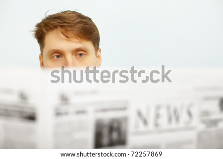 A young man reads the news in the newspaper - stock photo