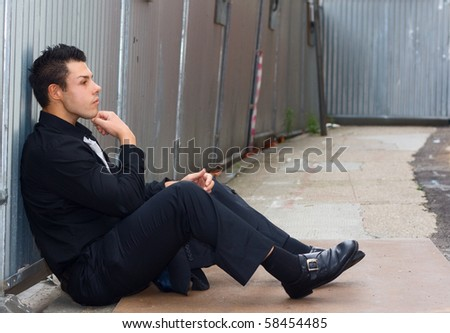 a young man reflecting on his life sitting on the floor. - stock photo