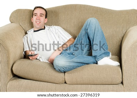 A young man relaxing on a couch and watching tv - stock photo