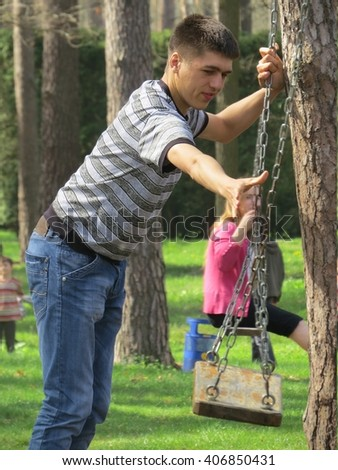A young man rides on a swing in the park.