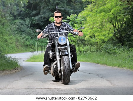 A young man riding a chopper on a road - stock photo
