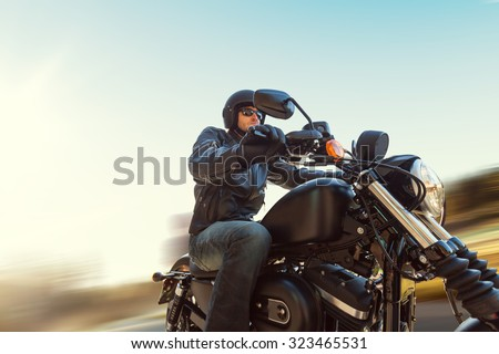 A young man riding a chopper on a road in blur motion - stock photo
