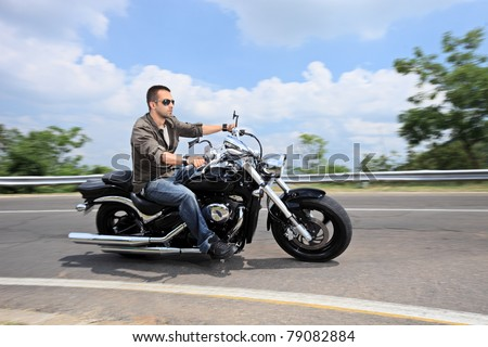 A young man riding a motorcycle on an open road - stock photo