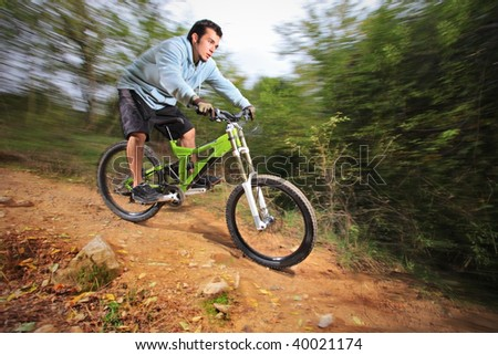 A young man riding a mountain bike downhill style - stock photo