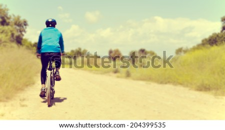a young man riding a mountain bike on a dirt road - stock photo
