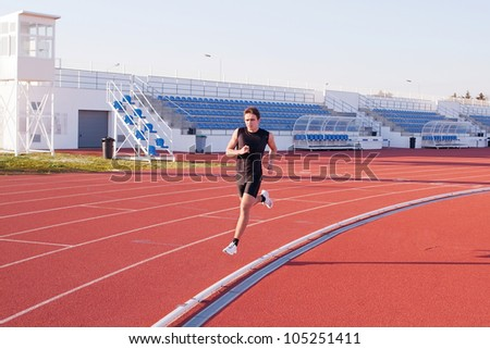 A young man run jogging in the stadium. - stock photo