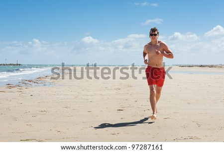 a young man running along the coast - stock photo