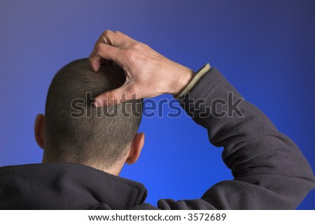 A young man scratches his head. Illustrates concepts of confusion and challenge. - stock photo