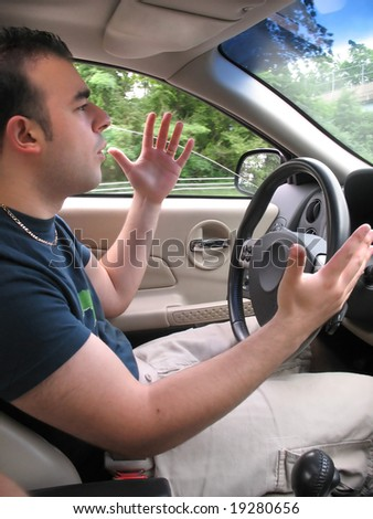 A young man seems to be experiencing some road rage while driving. - stock photo